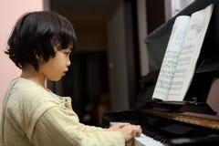 亚洲孩子钢琴使用 图库摄影