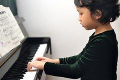 亚洲孩子钢琴使用 免版税库存照片