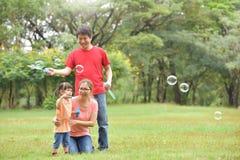 亚洲家庭一起吹肥皂泡 库存照片