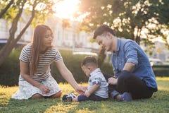 亚洲家庭在庭院里坐迷离背景,妈妈和爸爸照顾他们的草坪、生活方式和家庭的儿子 免版税库存图片