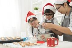亚洲家庭烘烤曲奇饼在厨房里 免版税库存照片