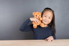 亚洲小女孩戏剧玩具熊画象  免版税库存照片
