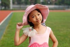 亚洲小女孩穿戴草帽 免版税库存图片