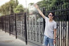 亚洲年轻人佩带的太阳镜户外 免版税库存照片