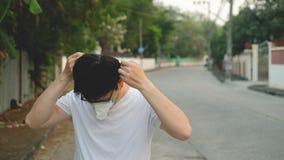 亚洲年轻人戴着N95面具为保护坏污染PM2 5与砖backgroundAsia年轻人的尘土戴着N95面具为保护ba 影视素材