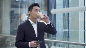 亚洲年轻发短信在电话的商人饮用的咖啡在商业中心 股票视频