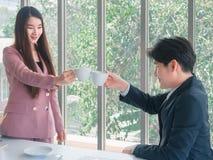 亚洲年轻英俊的商人和美好的女商人问候由咖啡 免版税库存图片
