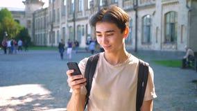 亚洲悦目男性移动他的电话并且扫视照相机冷颤,室外,都市心情 股票录像
