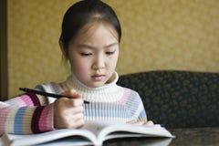 亚洲执行的女孩家庭作业 免版税库存图片
