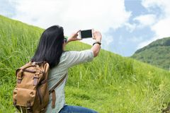 亚洲有背包用途手机的妇女旅客拍照片 库存图片