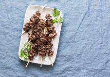 亚洲样式烤了在蓝色背景,顶视图的牛肉串 可口开胃菜,塔帕纤维布 免版税图库摄影