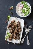 亚洲样式烤了牛肉串和细面条沙拉在黑暗的背景,顶视图 可口开胃菜,塔帕纤维布 免版税库存图片