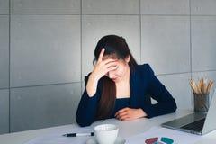 亚洲水军蓝色衣服张力的长发美丽的女商人与工作util头疼在她的办公室 有膝上型计算机,咖啡杯, 免版税图库摄影