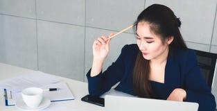 亚洲水军蓝色衣服的长发美丽的女商人考虑她的工作的解答的 她坐并且举行铅笔一会儿 免版税库存照片