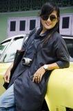 亚洲泰国妇女旅行和摆在与减速火箭的黄色经典汽车 免版税图库摄影