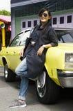 亚洲泰国妇女旅行和摆在与减速火箭的黄色经典汽车 库存照片