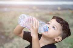 亚洲泰国孩子在公园喝水 免版税库存图片