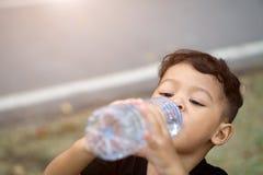 亚洲泰国孩子在公园喝水 库存图片