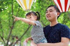 亚洲父亲容忍拥抱女儿爸爸爱女孩儿童游戏获得乐趣在公园室外夏日家庭活动愉快的童年 库存照片