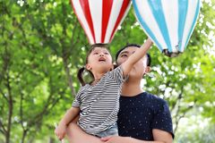 亚洲父亲容忍拥抱女儿爸爸爱女孩儿童游戏获得乐趣在公园室外夏日家庭活动愉快的童年 免版税库存照片
