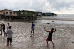 亚洲男孩服务排球海边镇可怜的年轻人Povert 库存图片