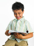 亚洲男孩杂志读取 免版税图库摄影