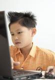 亚洲男孩计算机使用 免版税库存图片