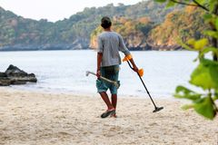 亚洲男性使用金属探测器发现在海滩的对象 免版税库存照片