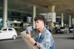 亚洲男性旅游读书地图,当等待出租汽车在空气时 库存图片