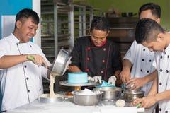 亚洲男性点心师愉快的工作队一起,当准备面团时 库存照片