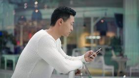 亚洲男性移动的电话外形在大窗口背景的  股票录像