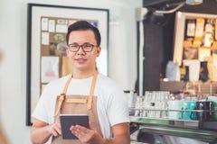 亚洲男性barista穿戴围裙举行片剂计算机咖啡菜单w 免版税库存图片