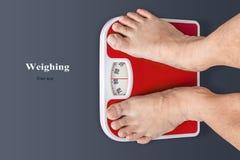 亚洲称在地磅台 他是非常肥胖的 免版税库存图片