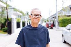 亚洲老人佩带的玻璃和看照相机画象在有汽车的住宅区和房子在背景中 库存图片