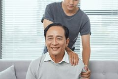 亚洲老人肩膀痛苦,坐沙发,按摩父亲肩膀的儿子 免版税库存图片