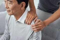 亚洲老人肩膀痛苦,坐沙发,按摩父亲肩膀的儿子 免版税库存照片