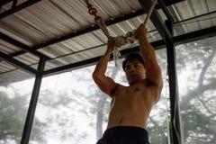 亚洲肌肉的人训练trx 免版税库存图片