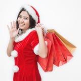 亚洲背景请求白种人中国圣诞节激动的帽子藏品查出的混合模型种族圣诞老人购物突出的空白冬天妇女年轻人 亚裔妇女在站立圣诞老人的帽子拿着购物袋 免版税库存图片