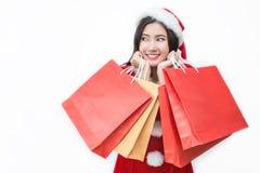 亚洲背景请求白种人中国圣诞节激动的帽子藏品查出的混合模型种族圣诞老人购物突出的空白冬天妇女年轻人 亚裔妇女在站立圣诞老人的帽子拿着购物袋 免版税图库摄影