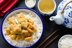 亚洲芝麻或teriyaki鸡用在碗、绿茶和筷子的米 免版税库存照片