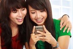 亚洲读取微笑的sms妇女年轻人 免版税库存照片