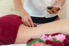 亚洲躺下在与传统巴厘语热的石头的按摩床上的秀丽妇女沿脊椎在泰国温泉和健康中心, 免版税库存图片