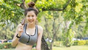 亚洲逗人喜爱的体育健康适合和牢固的亭亭玉立的青少年的女孩吃冰cre 免版税图库摄影