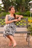亚洲长凳面对左坐的妇女 库存照片