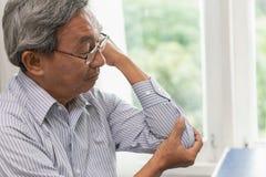 亚洲长辈遭受高尔夫球手肘痛苦 免版税库存照片