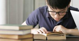 亚洲青少年的男孩留神镜片和使用的便携式计算机在家,做您的与严肃的面孔的逗人喜爱的男孩家庭作业 股票录像