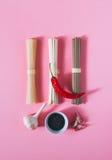 亚洲面条乌龙面和soba、红色辣椒、黑芝麻和大蒜在明亮的桃红色背景 免版税库存图片