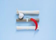 亚洲面条乌龙面和soba,红色辣椒,在明亮的蓝色背景的大蒜 免版税库存图片