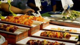 亚洲食物街道 在木串的完成的烤肉串有在柜台的菜的 股票录像