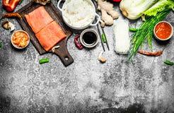 亚洲食物 与三文鱼和各种各样的成份片断的煮沸的米  在土气背景 免版税图库摄影